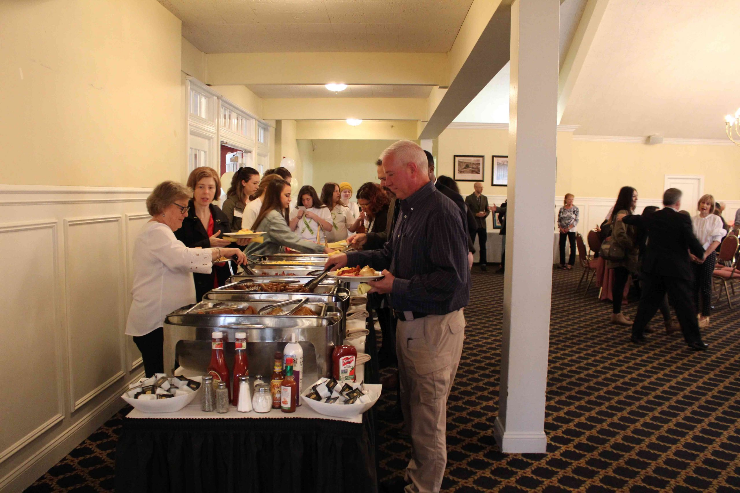 People lining up for buffet style breakfast at MHA Recognition Breakfast