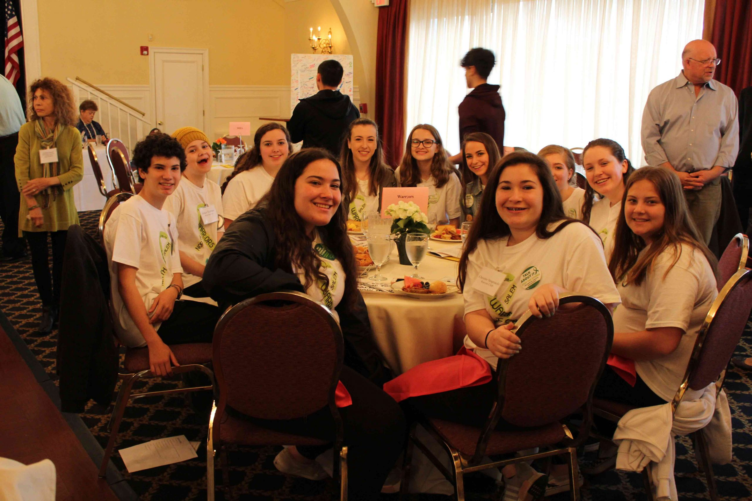 youth sitting down on table smiling for the camera at MHA Recognition Breakfast