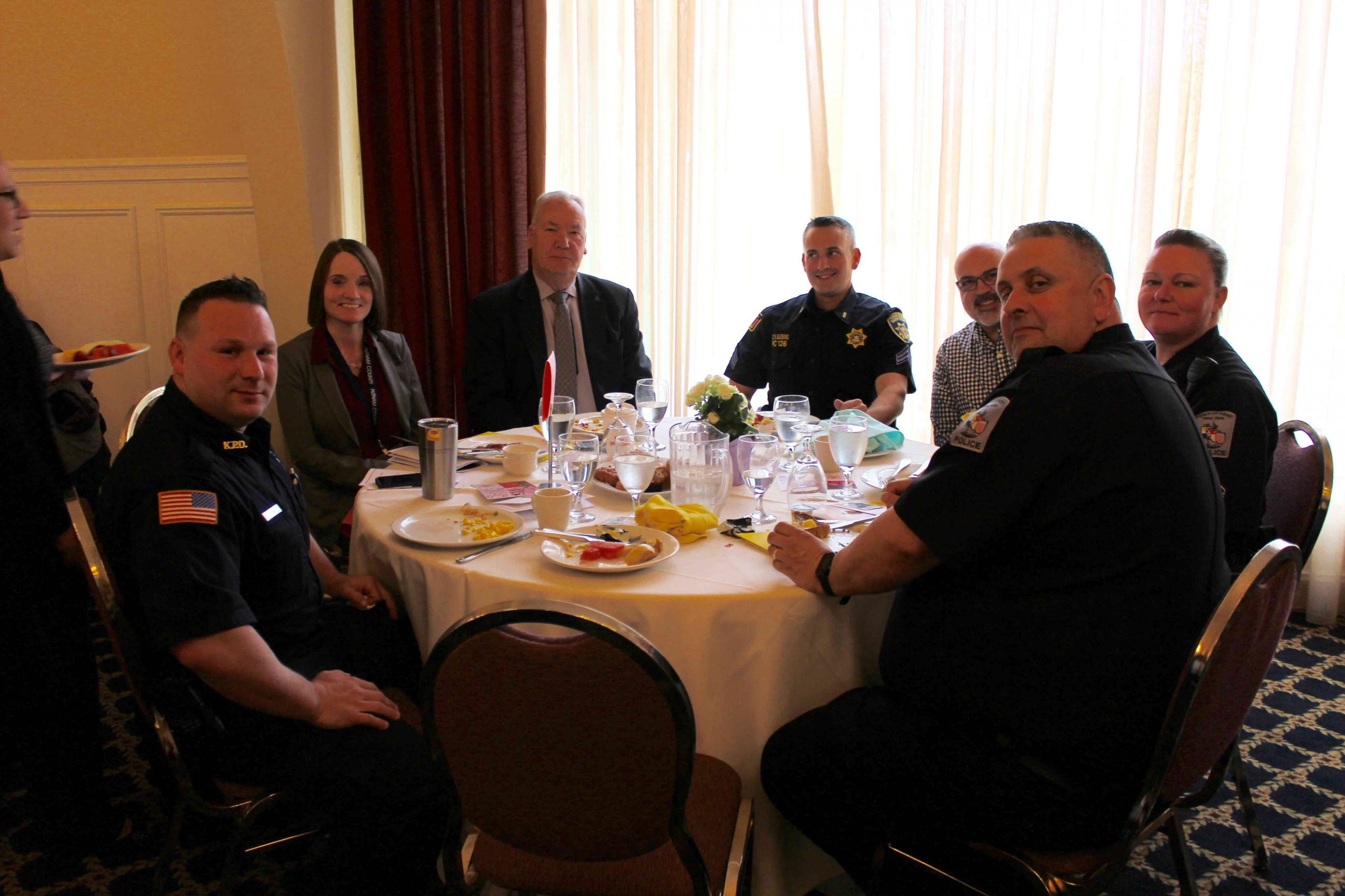group of police officers sitting down on table smiling for the camera at MHA Recognition Breakfast