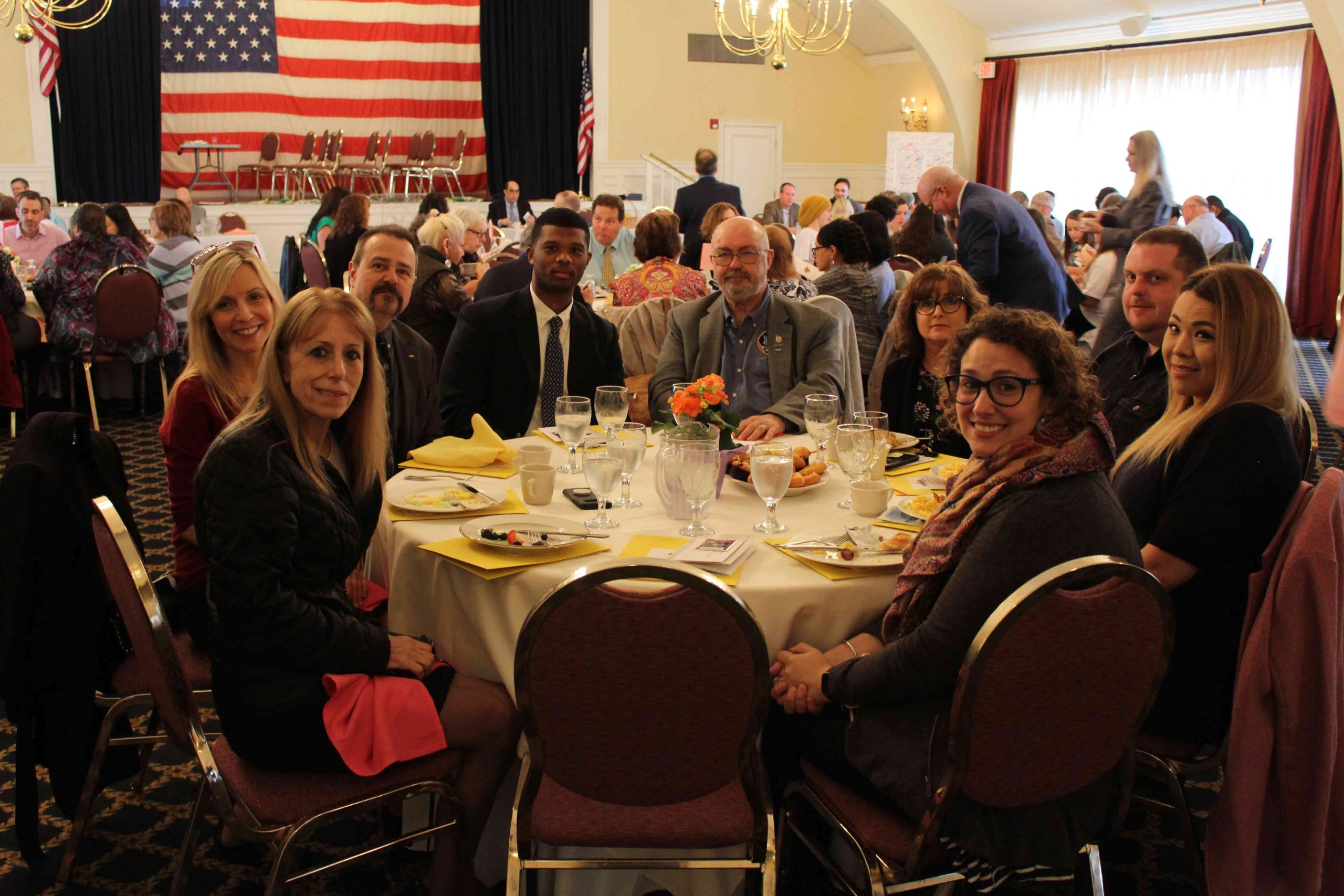 group of adults sitting down on table smiling for the camera at MHA Recognition Breakfast