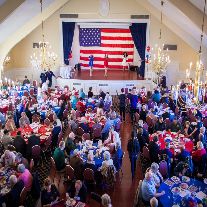 people sitting down looking at three woman sing infront of a big american flag at the MHA Putnam Veterans Chow Down