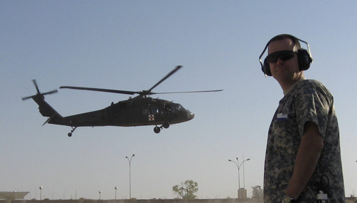 soldier standing up with helicopter in the background flying