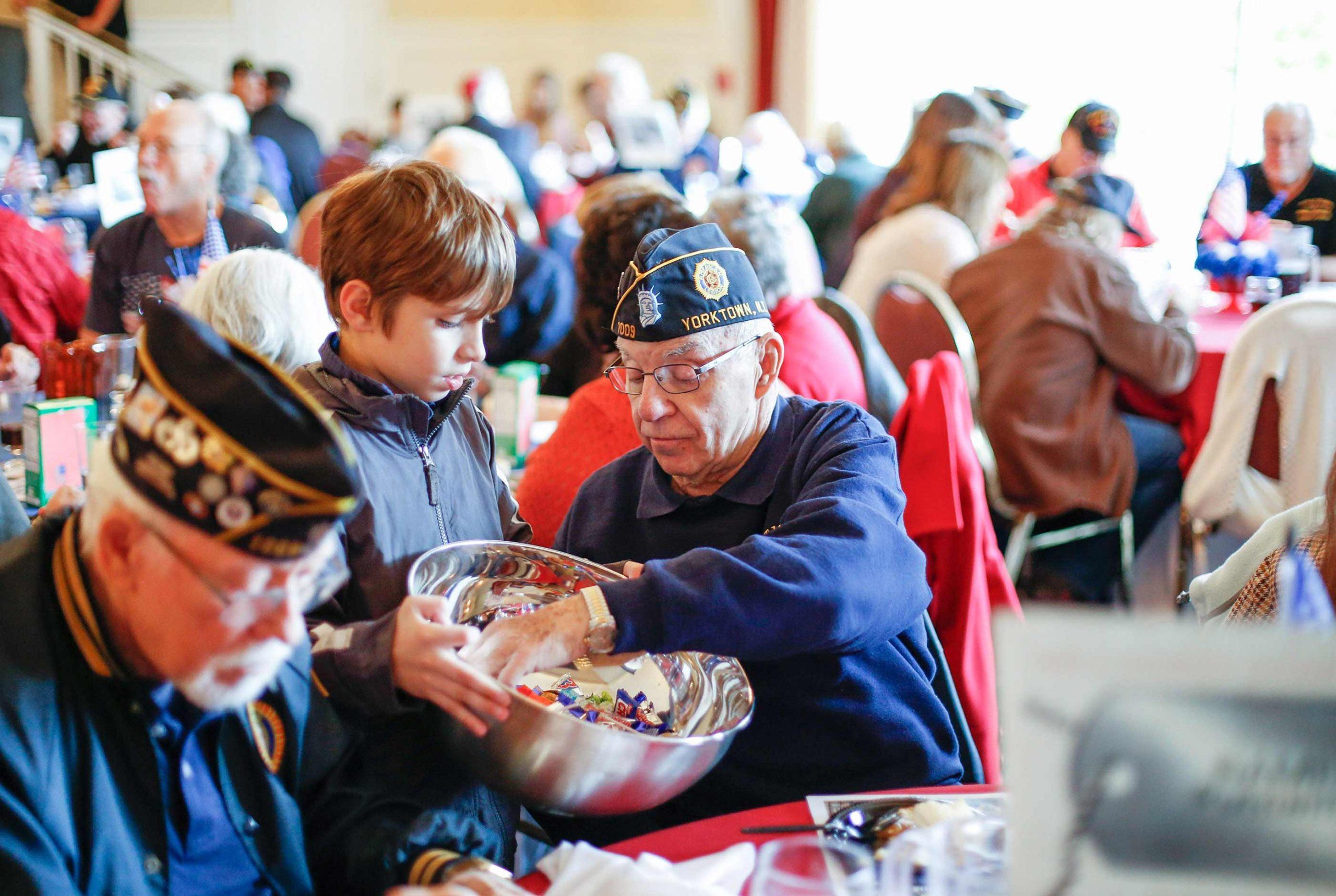 veteran sitting down with kid at the MHA Putnam Veterans Chow Down