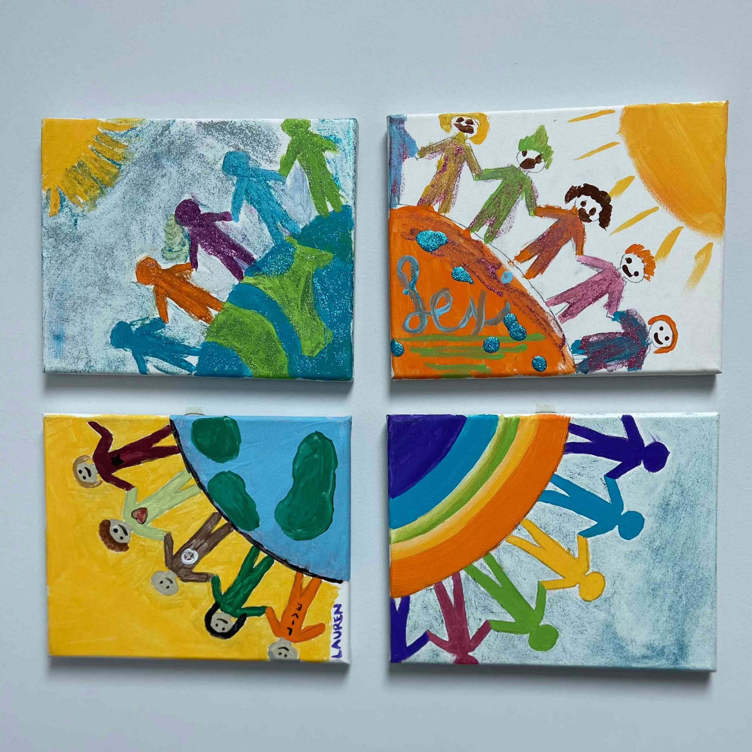 4 canvas painted with images of rainbows, suns, people, and the earth