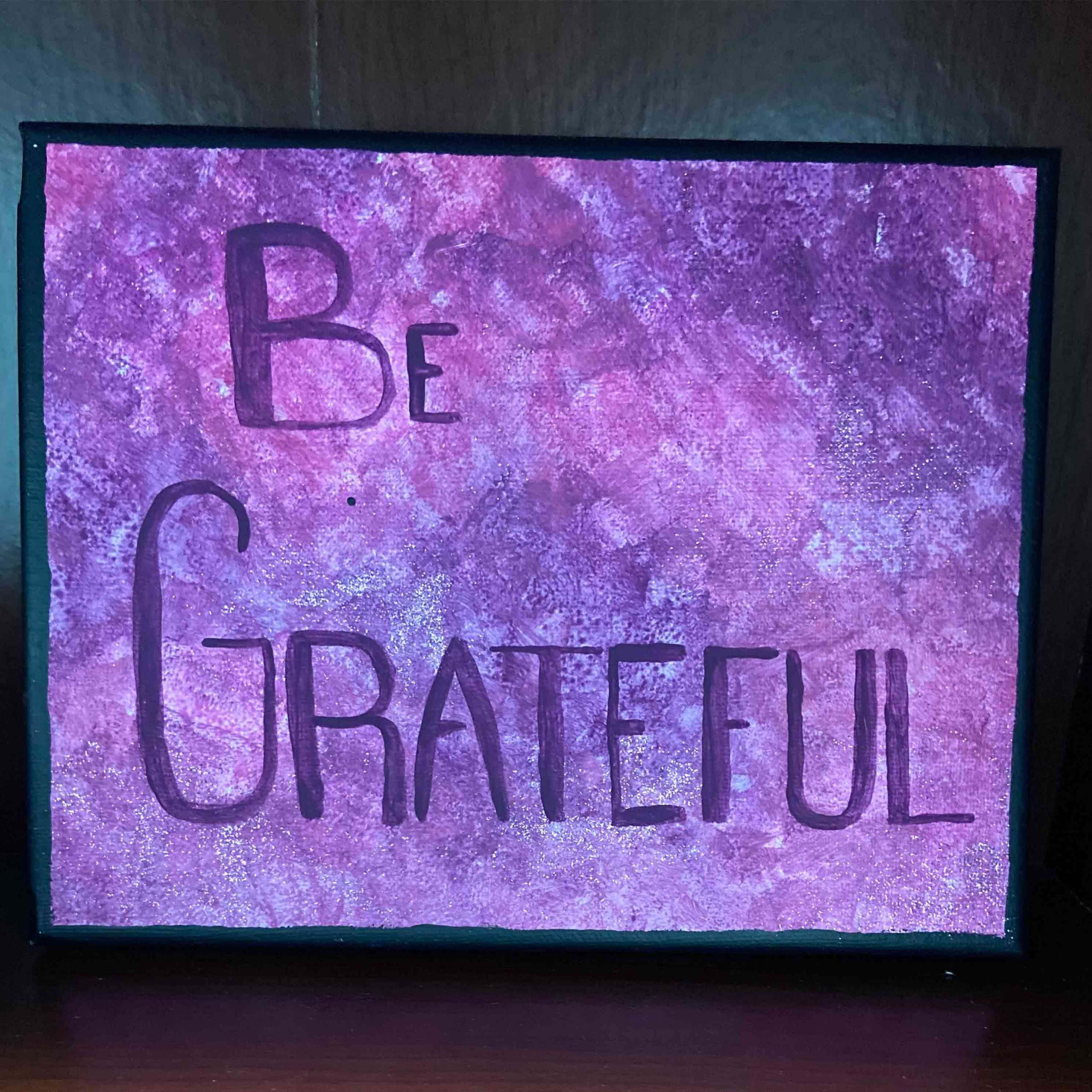 purple canvas painted with words that say Be Grateful