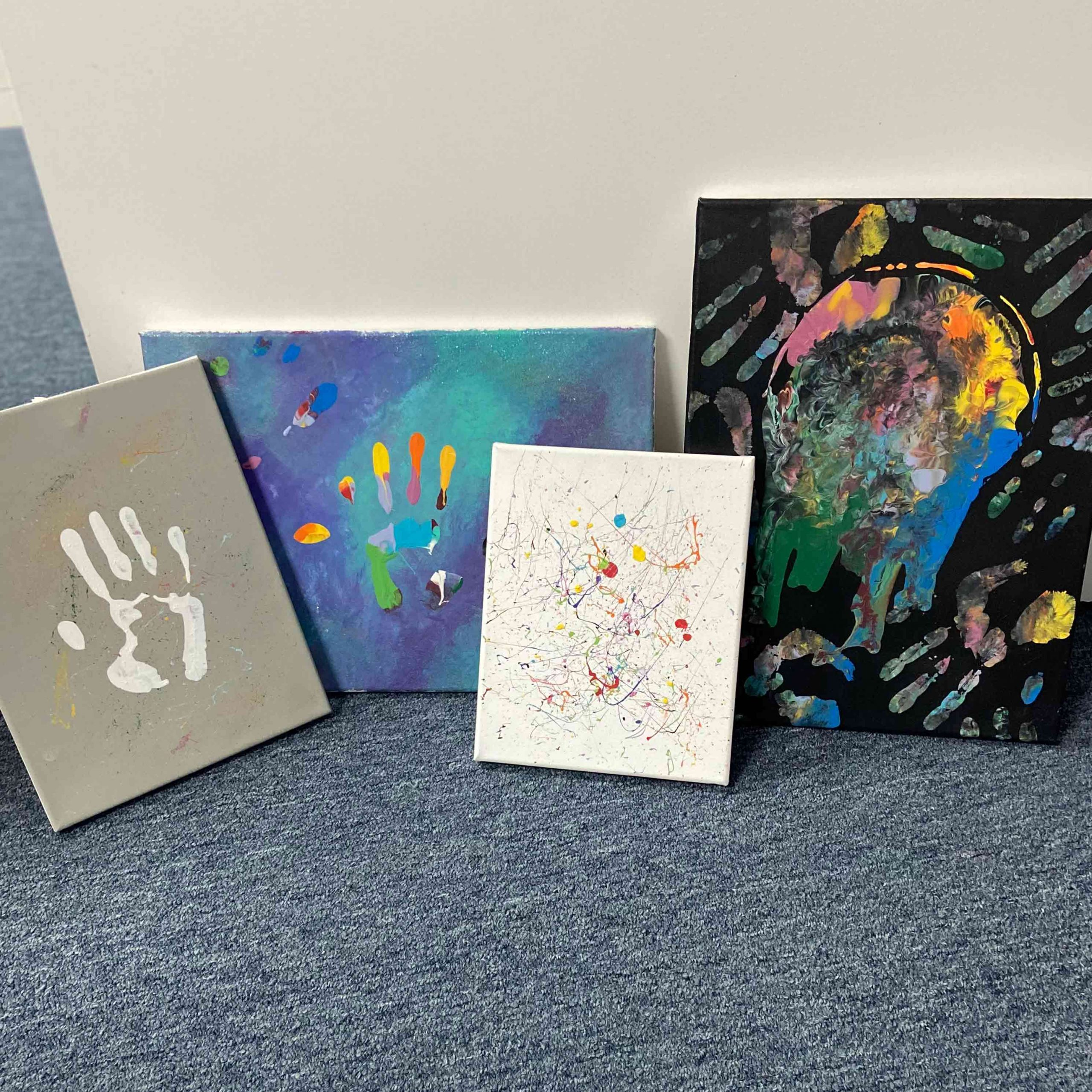 canvas on the floor with colorful paintings of hands and abstract pages