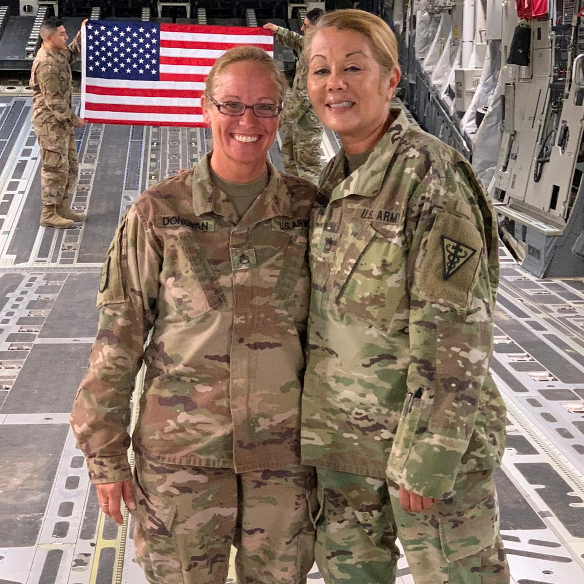 two women being deployed from base with usa flag behind